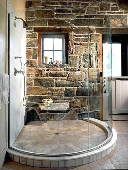 Piatto doccia circolare rivestito di mattoncini in pietra internamente e in marmo esternamente